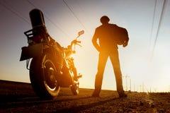 El motorista con la moto se coloca en el camino del cielo del contexto de la puesta del sol Fotos de archivo libres de regalías