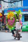 El motorista conduce las guirnaldas de la flor en Saigon Fotos de archivo