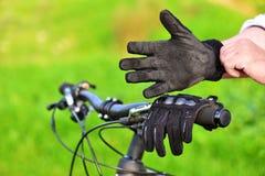 El motorista de la montaña desgasta guantes viejos Foto de archivo