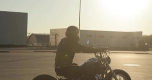 El motorista del hombre en la motocicleta está montando en el camino en ciudad en la luz hermosa de la puesta del sol metrajes