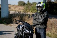 El motorista en casco en una motocicleta El motorista se coloca en el camino imagenes de archivo