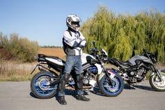 El motorista en casco en una motocicleta Viaje a una motocicleta El motorista se coloca en el camino fotos de archivo libres de regalías