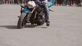 El motorista en una demostración de la motocicleta es paseos muy frescos y espectaculares en un círculo y hace vueltas hermosas a metrajes