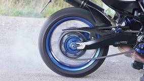 El motorista hace un truco con la rueda posterior de una bici en el asfalto almacen de metraje de vídeo
