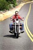 El motorista Helmetless monta el camino Curvy foto de archivo