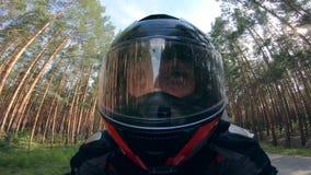 El motorista lleva el casco mientras que conduce en una moto almacen de metraje de vídeo