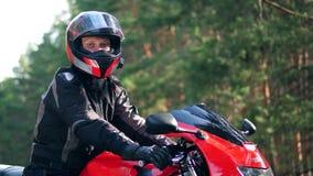 El motorista masculino en casco se sienta en una motocicleta, mirando la cámara almacen de video