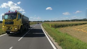 El motorista monta a lo largo del camino escénico entre los campos de maíz en Austria almacen de metraje de vídeo