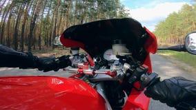 El motorista monta una bici roja, sosteniendo los manillares almacen de metraje de vídeo