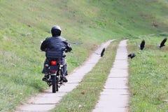 El motorista monta una motocicleta en el camino de las losas del cemento que dispersan cuervos Travesía en un caballo de hierro e imagen de archivo