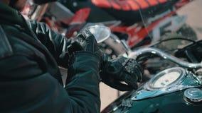 El motorista pone sus guantes de cuero de las manos y pone sus manos en el volante Él está consiguiendo listo para montar almacen de metraje de vídeo