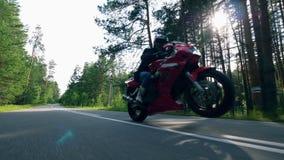 El motorista profesional hace trucos en un motocycle rojo metrajes