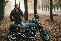 El motorista se sienta en una motocicleta vieja del café-corredor, fondo del otoño Imágenes de archivo libres de regalías