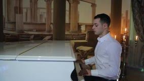 El movimiento de la cámara, hombre moreno lindo joven en la camisa blanca juega el piano de cola blanco metrajes