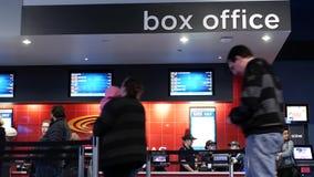El movimiento de la gente se alinea para el boleto de compra de la película en el cine