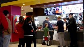 El movimiento de la gente se alinea para la comida que ordena en el contador de pago y envío de McDonalds
