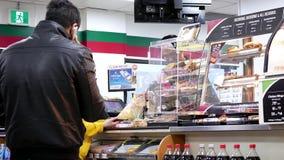 El movimiento de la gente se alinea para pagar la comida en el contador de pago y envío 7 once almacen de video