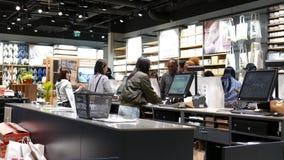 El movimiento de la gente se alinea para pagar los efectos de escritorio dentro de la tienda de Muji