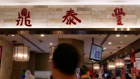 El movimiento de la gente se alinea para que el esperar entre en el restaurante de Tai Fung del dinar