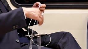 El movimiento del hombre de negocios enchufa el auricular para la música que escucha mientras que toma el MRT