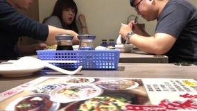 El movimiento del menú de la lectura del cliente y la gente disfrutan de la comida