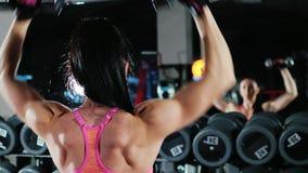 El movimiento hacia la meta y la motivación: entrenamiento atlético de la mujer con una opinión trasera de la pesa de gimnasia metrajes