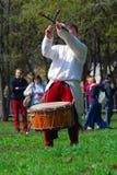 El músico en trajes históricos se realiza en un parque Él juega los tambores Imagen de archivo libre de regalías