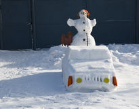 El muñeco de nieve conduce el coche en un año de un gallo Imagen de archivo