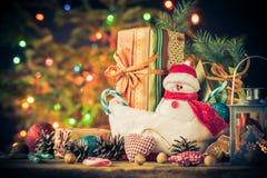 El muñeco de nieve de la tarjeta de Navidad adorna el fondo de las luces del árbol de los regalos Fotografía de archivo