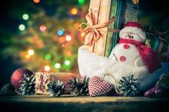 El muñeco de nieve de la tarjeta de Navidad adorna el fondo de las luces del árbol de los regalos Imagen de archivo