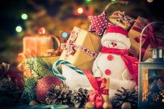 El muñeco de nieve de la tarjeta de Navidad adorna el fondo de las luces del árbol de los regalos Fotografía de archivo libre de regalías