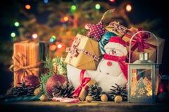 El muñeco de nieve de la tarjeta de Navidad adorna el fondo de las luces del árbol de los regalos Foto de archivo