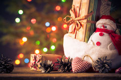 El muñeco de nieve de la tarjeta de Navidad adorna el fondo de las luces del árbol de los regalos Imagenes de archivo