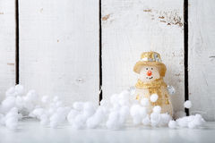 El muñeco de nieve de la vela y la bola de la nieve adornan por Feliz Año Nuevo de la Feliz Navidad en el fondo de madera blanco  Fotografía de archivo
