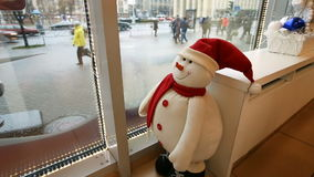 El muñeco de nieve divertido del juguete mira del café a la calle almacen de metraje de vídeo
