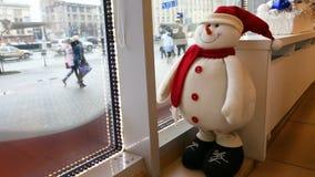 El muñeco de nieve divertido del juguete mira del café a la calle metrajes