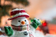 El muñeco de nieve entre la pila de nieve en la noche silenciosa con una bombilla, enciende para arriba la esperanza y la felicid Imagen de archivo