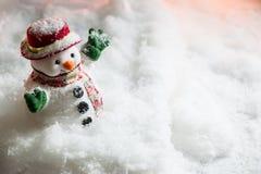 El muñeco de nieve entre la pila de nieve en la noche silenciosa con una bombilla, enciende para arriba la esperanza y la felicid Imagenes de archivo
