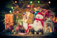 El muñeco de nieve de la tarjeta de Navidad adorna el fondo de las luces del árbol de los regalos Fotos de archivo