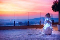 El muñeco de nieve lindo que mira el sol va abajo en terraza del tejado Imagenes de archivo