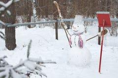 El muñeco de nieve se coloca en la nieve con una escoba y una pala Imagenes de archivo
