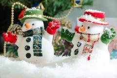 El muñeco de nieve y la bombilla se colocan entre la pila de nieve en la noche silenciosa, encienden para arriba la esperanza y l Foto de archivo libre de regalías