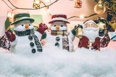 El muñeco de nieve y Papá Noel sostienen la campana entre la pila de nieve en la noche silenciosa con una bombilla, encienden par Fotografía de archivo