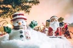 El muñeco de nieve y Papá Noel sostienen la campana entre la pila de nieve en la noche silenciosa con una bombilla, encienden par Imagen de archivo libre de regalías