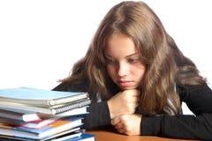 El muchacha-adolescente mira la pila de libros Imágenes de archivo libres de regalías