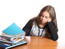 El muchacha-adolescente mira la pila de libros Fotos de archivo libres de regalías