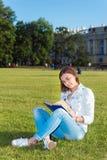 el Muchacha-estudiante se sienta en césped y lee el libro de textos Imagen de archivo libre de regalías