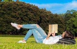 el Muchacha-estudiante se sienta en césped y lee el libro de textos Foto de archivo libre de regalías