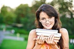 el Muchacha-estudiante sostiene los libros de textos Fotografía de archivo libre de regalías
