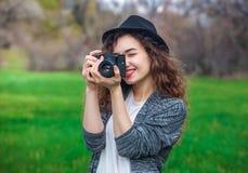El muchacha-fotógrafo hermoso con el pelo rizado que sostiene una cámara vieja y toma una imagen Foto de archivo